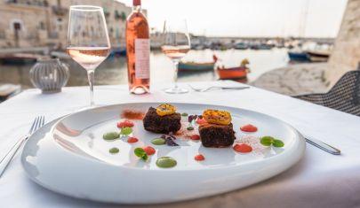 Il mare di Giovinazzo sullo sfondo, un calice in mano, una selezione di crudo nel piatto: di più non si può